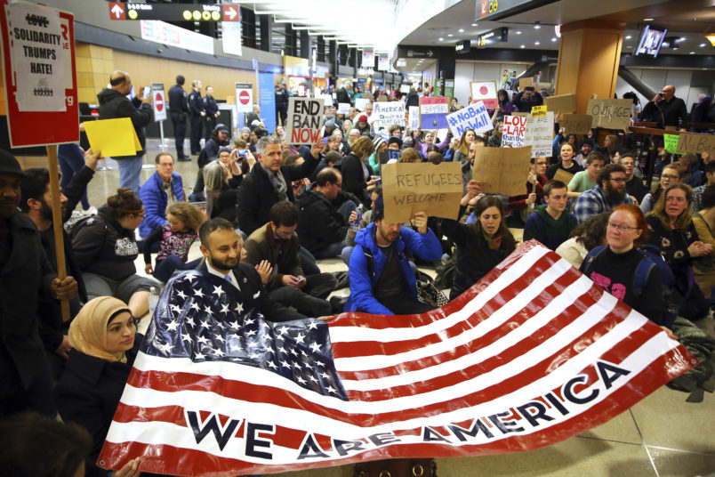 "Demonstrators sit down in the concourse and hold a sign that reads ""We are America."" More than 1,000 people gather at Seattle-Tacoma International Airport, Saturday, January 28 to protest President Trump's immigration ban.President Trump signed an executive order Friday that bars citizens from Iraq, Syria, Iran, Libya, Somalia, Sudan and Yemen from entering the U.S. for the next 90 days and suspends the admission of all refugees for 120 days. (AP Photo/seattlepi.com, Genna Martin)"
