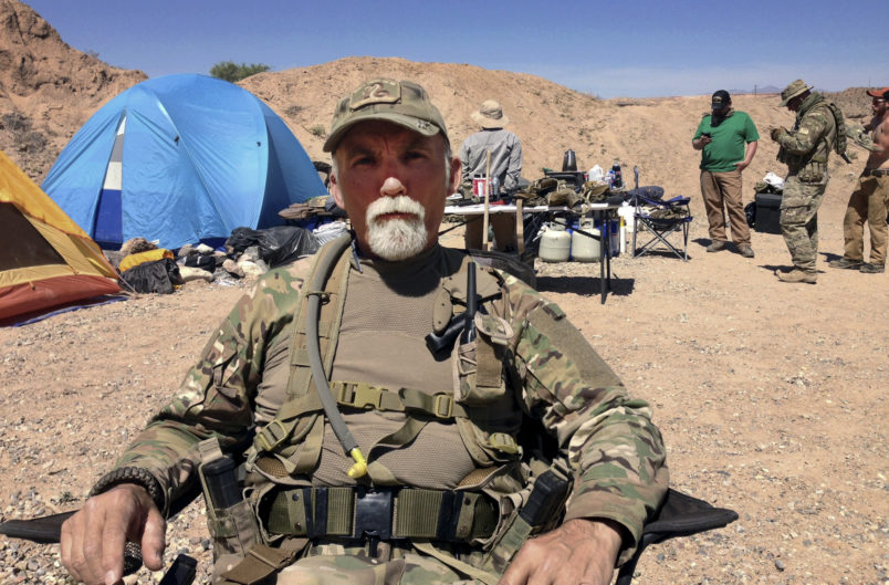 FILE - In this April 16, 2014 file photo, Jerry DeLemus, of Rochester, N.H., sits with a group of self-described militia members camping on rancher Cliven Bundy's ranch near Bunkerville, Nev. Delemus one of two defendants are set to become the first to plead guilty in Nevada to federal charges stemming from an armed confrontation with U.S. land management agents near Nevada rancher Cliven Bundy's ranch in 2014.DeLemus of New Hampshire is expected to enter his plea Tuesday, Aug. 23. (AP Photo/Ken Ritter, File)
