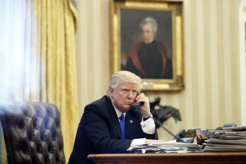 President Donald Trump speaks on the phone with Prime Minister of Australia Malcolm Turnbull in the Oval Office of the White House, Saturday, Jan. 28, 2017 in Washington. (AP Photo/Alex Brandon)