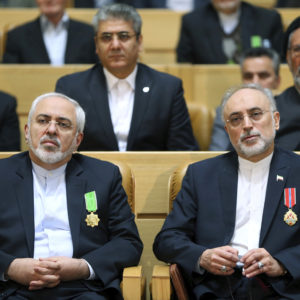 FILE-- In this file photo taken on Monday, Feb. 8, 2016, chief of Iran's Atomic Energy Organization Ali Akbar Salehi, right, sits next to Foreign Minister Mohammad Javad Zarif after being awarded medal of honor by President Hassan Rouhani during a ceremony in Tehran, Iran.  Iran's atomic chief warned Tuesday the Islamic Republic needs only five days to ramp up its uranium enrichment to 20 percent, a level at which the material could be used for a nuclear weapon. (AP Photo/Ebrahim Noroozi, File)