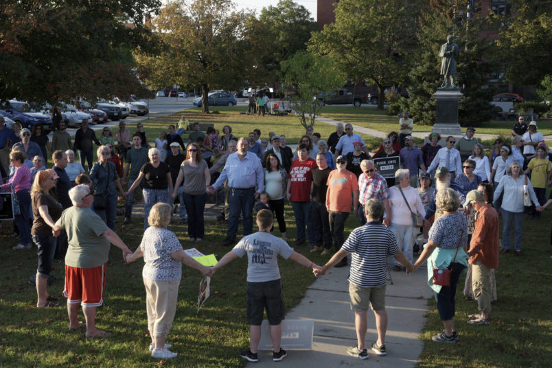"""A chorus of """"We Shall Overcome"""" rises from a gathering against racism in Broad Street Park in Claremont, N.H., Tuesday, September 12, 2017. The demonstration was inspired by violence last month against an 8-year-old biracial boy that occurred while he played with a group of teenagers outside his home. (AP Photo/Valley News, James M. Patterson)"""