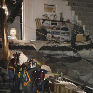 Rescue workers evacuate by rain the collapsed office building at the corner of Alvaro Obregon and Yucatan streets in Mexico City, early Monday Sept 25, 2017. Search teams are still digging in dangerous piles of rubble hoping against the odds to find survivors at collapsed buildings. (AP Photo/Miguel Tovar)
