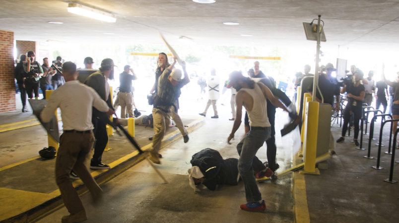 HFM for PM story**In this Saturday, Aug. 12, 2017 image provided by by Zach D. Roberts, Deandre Harris, bottom is assaulted in a parking garage beside the Charlottesville police station after a white nationalist rally was disbursed by police, in Charlottesville, Va. (Zach D. Roberts via AP)