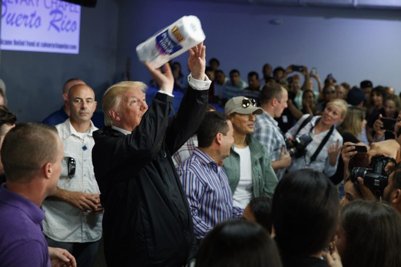 President Donald Trump tosses paper towels into a crowd as he hands out supplies at Calvary Chapel, Tuesday, Oct. 3, 2017, in Guaynabo, Puerto Rico. (AP Photo/Evan Vucci)