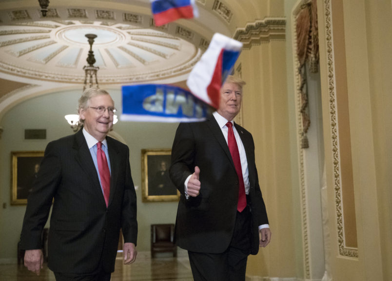 Small Russian flags are thrown by a protester as President Donald Trump, escorted by Senate Majority Leader Mitch McConnell, R-Ky., arrives on Capitol Hill to have lunch with Senate Republicans and push for his tax reform agenda, in Washington, Tuesday, Oct. 24, 2017. (AP Photo/J. Scott Applewhite)