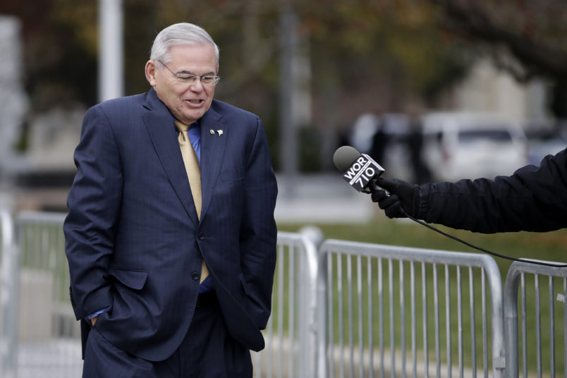 U.S. Sen. Bob Menendez, center, shrugs as a reporter asks him a questions while leaving the Martin Luther King Jr. Federal Courthouse after stopping in to appear on his corruption trial, Tuesday, Nov. 14, 2017, in Newark, N.J. Jury deliberations in the bribery trial of Menendez are scheduled to continue amid uncertainty over the fallout from comments made by an excused juror last week. The juror told reporters on Thursday, Nov. 9, that although many jurors appeared to be leaning toward acquittal, she anticipated a hung jury. (AP Photo/Julio Cortez)