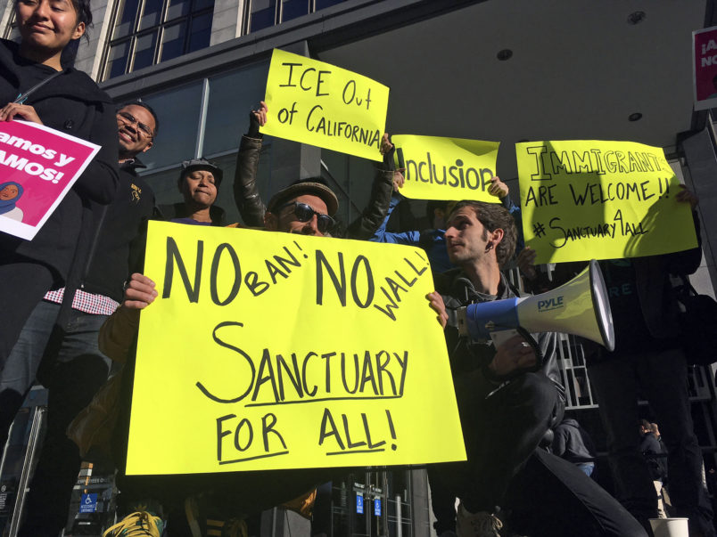 FILE - In this April 14, 2017, file photo, protesters hold up signs outside a courthouse where a federal judge was to hear arguments in the first lawsuit challenging President Donald Trump's executive order to withhold funding from communities that limit cooperation with immigration authorities in San Francisco.  A federal judge Monday, Nov. 20, 2017 has permanently blocked President Donald Trump's executive order to cut funding from cities that limit cooperation with U.S. immigration authorities. San Francisco and Santa Clara County had filed lawsuits. (AP Photo/Haven Daley, File)