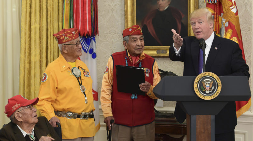 President Donald Trump, right, speaks during a meeting with Navajo Code Talkers including Thomas Begay, second from left, and Peter MacDonald, second from right, in the Oval Office of the White House in Washington, Monday, Nov. 27, 2017. (AP Photo/Susan Walsh)