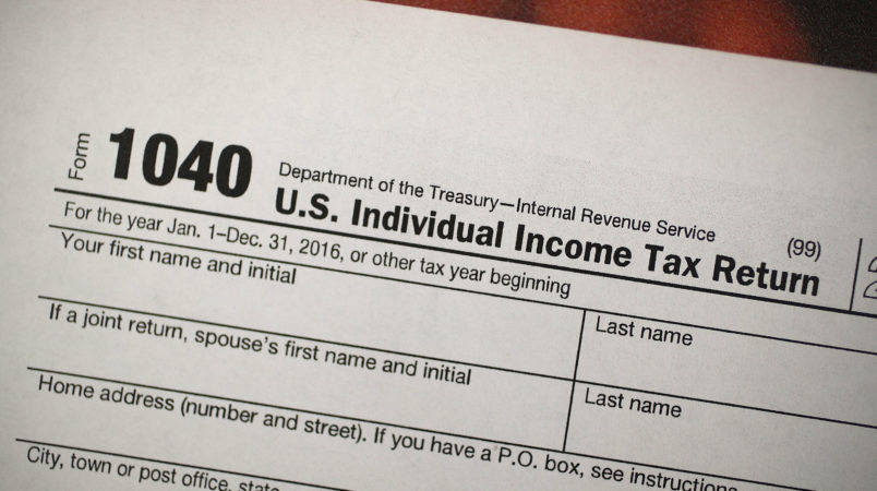 """MIAMI, FL - DECEMBER 22:  A copy of a IRS 1040 tax form is seen at an H&R Block office on the day President Donald Trump signed the Republican tax cut bill in Washington, DC  on December 22, 2017 in Miami, Florida. Kathy Pickering, vice president of regulatory affairs and executive director of The Tax Institute at H&R Block released a statement about the new tax bill saying, """" ItÕs going to change the way you think about and plan your income taxes. YouÕll need to take a fresh look at your individual situation to know your outcome and new strategies to use to get the best tax outcome.Ó  (Photo by Joe Raedle/Getty Images)"""