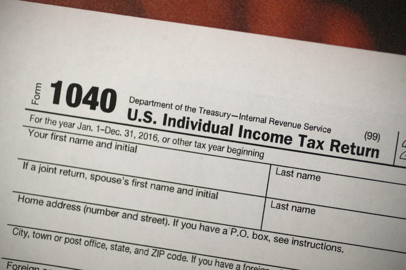 "MIAMI, FL - DECEMBER 22:  A copy of a IRS 1040 tax form is seen at an H&R Block office on the day President Donald Trump signed the Republican tax cut bill in Washington, DC  on December 22, 2017 in Miami, Florida. Kathy Pickering, vice president of regulatory affairs and executive director of The Tax Institute at H&R Block released a statement about the new tax bill saying, "" ItÕs going to change the way you think about and plan your income taxes. YouÕll need to take a fresh look at your individual situation to know your outcome and new strategies to use to get the best tax outcome.Ó  (Photo by Joe Raedle/Getty Images)"