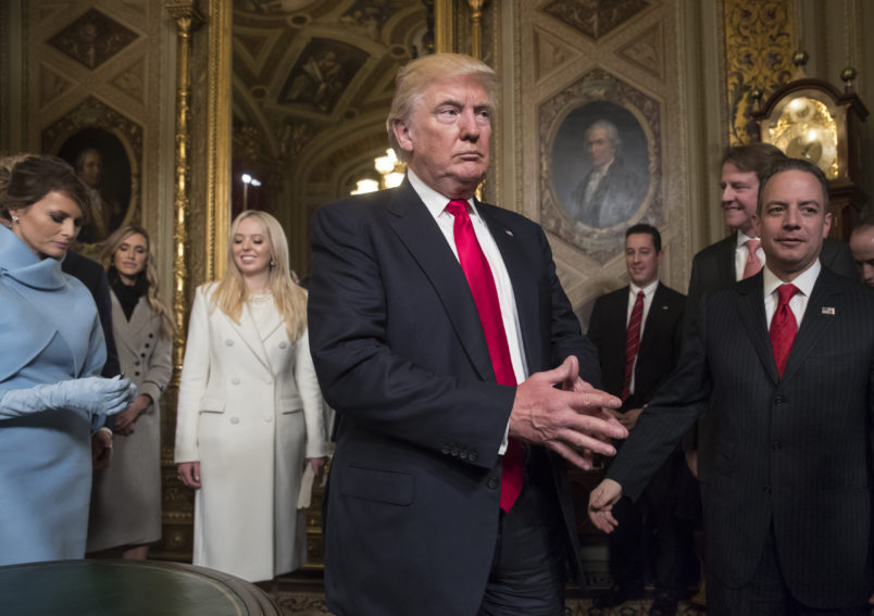 President Donald Trump leaves the President's Room of the Senate at the Capitol after he formally signed his cabinet nominations into law, in Washington, Friday, Jan. 20, 2017. He is joined by his wife Melania Trump and  and daughter Tiffany Trump. At far right is Chief of Staff Reince Priebus, with White House counsel Donald McGahn, second from right. (AP Photo/J. Scott Applewhite, Pool)