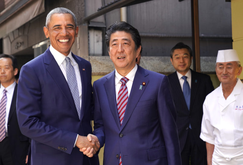 Former U.S. President Barack Obama and Japanese Prime Minister Shinzo Abe pose for photographers in front of Japanese Sushi restaurant in Tokyo's Ginza shopping district, Sunday, March 25, 2018. (AP Photo/Shizuo Kambayashi, Pool)