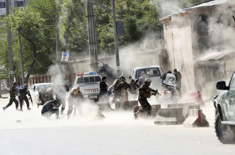Security forces run from the site of a suicide attack one frame after the second deadly attack in Kabul, Afghanistan, Monday, April 30, 2018.  (AP Photo/Massoud Hossaini)