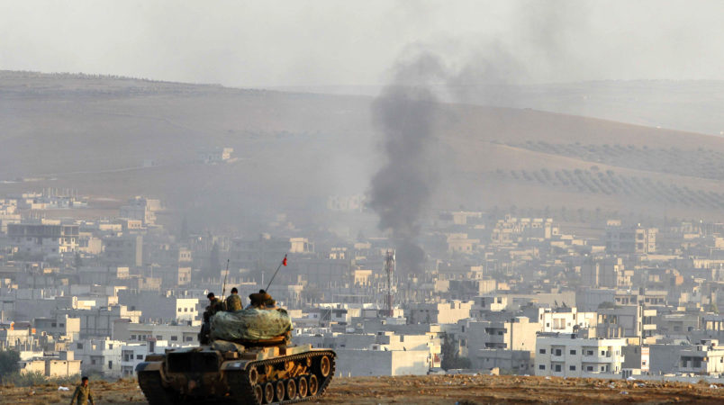 SANLIURFA, TURKEY -  OCTOBER 9: Turkish soldiers on a tank hold their positions on a hilltop in the outskirts of Suruc, Turkey, at the Turkey-Syria border, overlooking smoke rising from a strike in Kobani, Syria, during fighting between Syrian Kurds and the militants of Islamic State group, Thursday, Oct. 9, 2014. Kobani, also known as Ayn Arab, and its surrounding areas, has been under assault by extremists of the Islamic State group since mid-September and is being defended by Kurdish  fighters. (Photo by Gokhan Sahin/Getty Images)