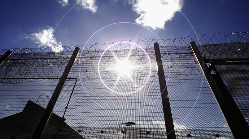 NORWICH, UNITED KINGDOM - AUGUST 25:  (EDITORS NOTE: IMAGES EMBARGOED FOR PUBLICATION UNTIL 0001GMT AUGUST 26, 2005; NATURAL LENS FLARE VISIBLE IN IMAGE) The sun shines through high security fencing surrounding Norwich Prison on August 25, 2005 in Norwich, England. A Chief Inspector of Prisons report on Norwich Prison says healthcare accommodation was among the worst seen, as prisoners suffered from unscreened toilets, little natural light, poor suicide prevention, inadequate education and training for long-term prisoners. (Photo by Peter Macdiarmid/Getty Images)