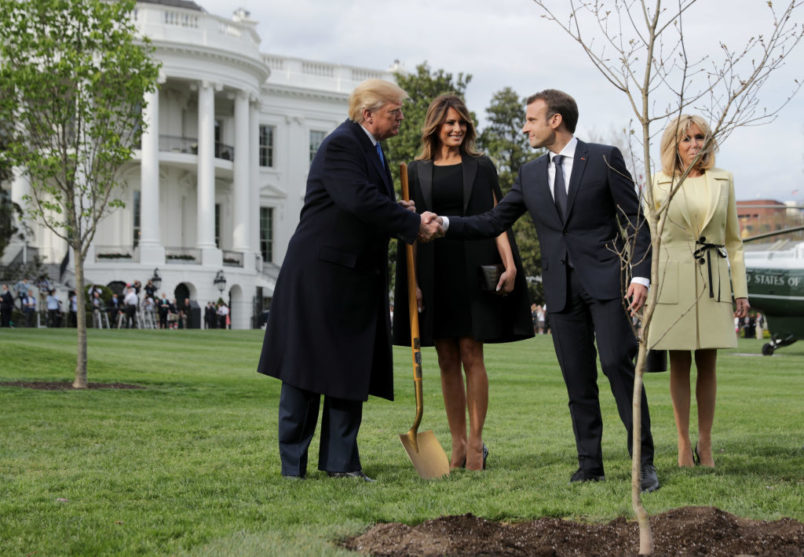 """WASHINGTON, DC - APRIL 23:  U.S. President Donald Trump, U.S. first lady Melania Trump, French President Emmanuel Macron and his wife Brigitte Macron participate in a tree-planting ceremony on the South Lawn of the White House April 23, 2018 in Washington, DC. The European Sessile Oak is a gift from the Macrons and comes from Belleau Woods, where more than 9,000 American marines died in June 1918 during the First World War. According to the first lady's office """"The forest is a memorial site and important symbol of the sacrifice the United States made to ensure peace and stability in Europe."""" (Photo by Chip Somodevilla/Getty Images)"""
