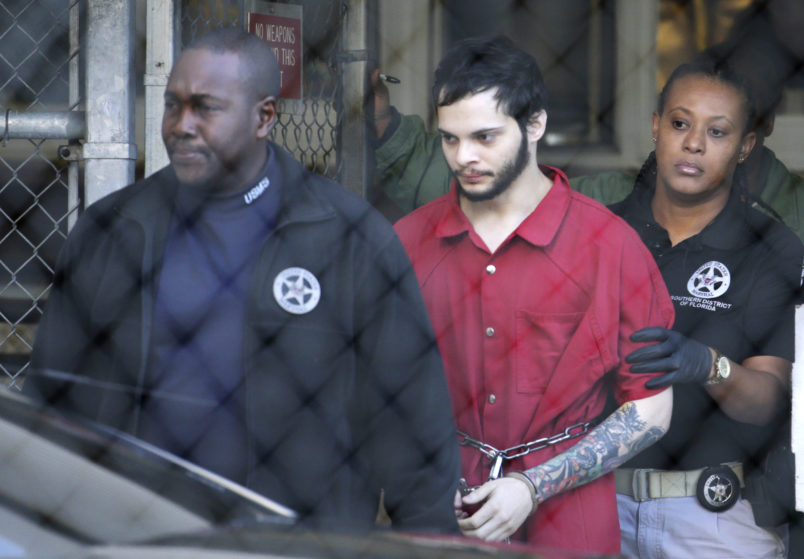 FILE - In this Jan. 30, 2017, file photo, Esteban Santiago, center, is led from the Broward County jail for an arraignment in federal court in Fort Lauderdale, Fla. Court records say Santiago charged with killing five people and wounding six in a shooting rampage at a Florida airport has been found mentally competent and is scheduled to plead guilty later in May 2018. Federal prosecutors said in a court filing late Monday, Monday, May 14, 2018, that Santiago was recently evaluated by a psychologist. (AP Photo/Lynne Sladky, File)