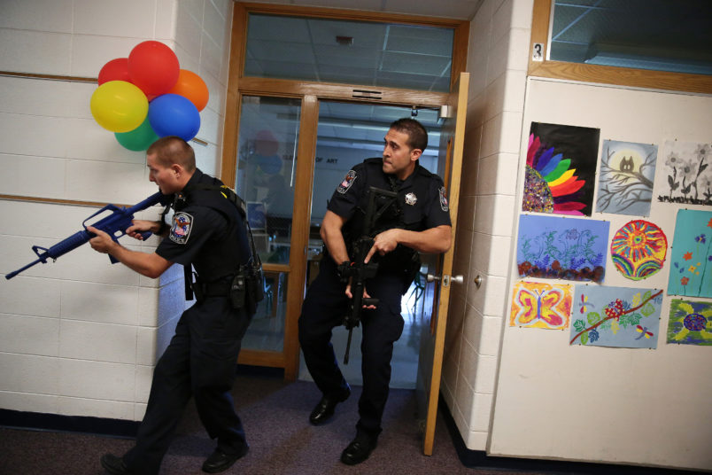 Two Cary police officers, including officer Anthony Tangorra, at right, carry blank weapons as they participate in an active shooter exercise with police, emergency workers, teachers and administrators Saturday, Sept. 12, 2015 at Oak Knoll School in Cary, Ill. (Anthony Souffle/Chicago Tribune/TNS)