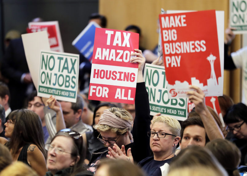 """People attending a Seattle City Council meeting hold signs that read """"Tax Amazon, Housing for All,"""" and """"No Tax on Jobs"""" listen to public comment on the debate over a possible council vote whether or not to repeal of a tax on large companies such as Amazon and Starbucks that was intended to combat a growing homelessness crisis, Tuesday, June 12, 2018, at City Hall in Seattle. (AP Photo/Ted S. Warren)"""