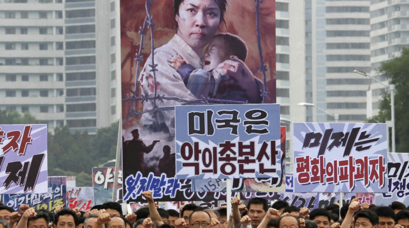 "Tens of thousands of men and women pump their fists in the air and chant as they carry placards with anti-American propaganda slogans at Pyongyang's central Kim Il Sung Square on Sunday, June 25, 2017, in North Korea, to mark what North Korea calls ""the day of struggle against U.S. imperialism"" – the anniversary of the start of the Korean War. (AP Photo/Jon Chol Jin)"