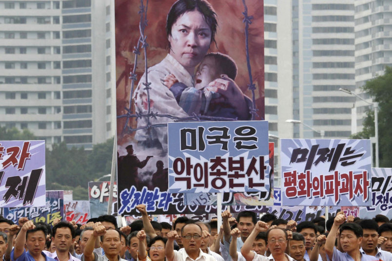 """Tens of thousands of men and women pump their fists in the air and chant as they carry placards with anti-American propaganda slogans at Pyongyang's central Kim Il Sung Square on Sunday, June 25, 2017, in North Korea, to mark what North Korea calls """"the day of struggle against U.S. imperialism"""" – the anniversary of the start of the Korean War. (AP Photo/Jon Chol Jin)"""