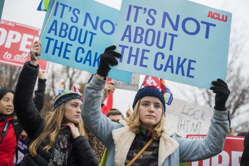 UNITED STATES - DECEMBER 05: Lydia Macy, right, of Berkeley, Calif., siding with a same-sex couple, holds a sign outside Supreme Court where arguments were being on heard on whether a Colorado baker, who refused to make a wedding cake for the couple based on his religious beliefs, is protected by the First Amendment on December 5, 2017. (Photo By Tom Williams/CQ Roll Call)