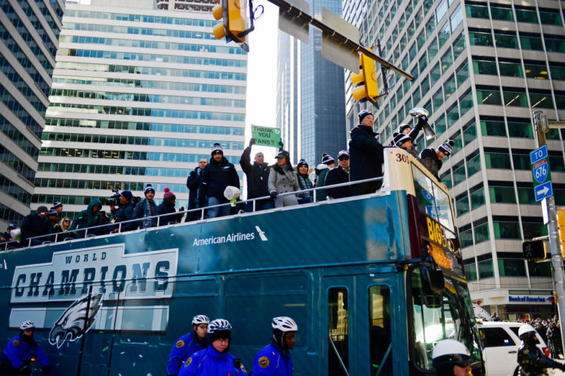 PHILADELPHIA, PA - FEBRUARY 08: (L-R) Team owner Jeffrey Lurie, with quarterbacks Nick Foles #9, Nate Sudfeld #7 and Carson Wentz #11 of the Philadelphia Eagles, acknowledge fans as Sudfeld hoists the Vince Lombardi Trophy atop a parade bus during festivities on February 8, 2018 in Philadelphia, Pennsylvania. The city celebrated the Philadelphia Eagles' Super Bowl LII championship with a victory parade. (Photo by Corey Perrine/Getty Images)