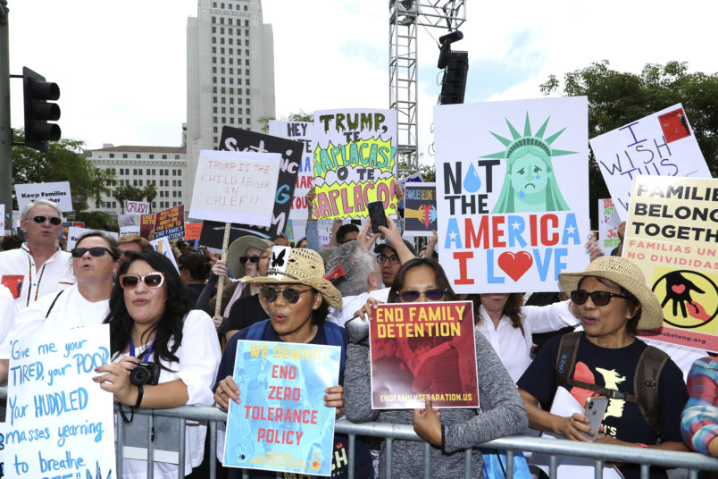 "People hold signs as they participate in the ""Families Belong Together: Freedom for Immigrants"" march on Saturday, June 30, 2018, in Los Angeles. In major cities and tiny towns, marchers gathered across America, moved by accounts of children separated from their parents at the U.S.-Mexico border, in the latest act of mass resistance against President Donald Trump's immigration policies.(Photo by Willy Sanjuan/Invision/AP)"