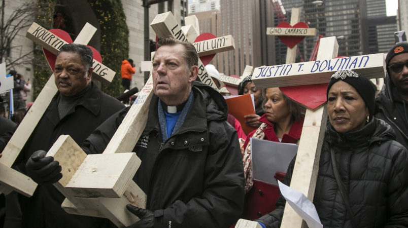 FILE -  In this Dec. 31, 2016 file photo, The Rev. Michael Pfleger, center, Rev. Jesse Jackson, left, and state Sen. Jacqueline Collins, right, led hundreds in a march down Michigan Avenue, carrying crosses for all those killed by Chicago violence in 2016 and to call for an end to violence in Chicago. Protesters planning to shut down a major Chicago interstate on Saturday, July 7, 2018, say they're trying to increase pressure on public officials to address the gun violence that's claimed hundreds of lives in some of the city's poorest neighborhoods. (Ashlee Rezin/Chicago Sun-Times via AP)
