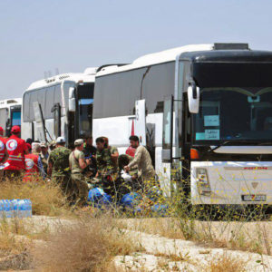 In this photo released by the Syrian official news agency SANA, Syrian government forces and Syrian Arab Red Crescent oversee the evacuation by buses of opposition fighters and their families from the southern province of Daraa, Syria, Sunday, July 15, 2018. The evacuation deal will hand over areas held by the rebels for years back to government control. Daraa, which lies on a highway linking Damascus with Jordan, was the cradle of the 2011 uprising against Syrian President Bashar Assad. (SANA via AP)