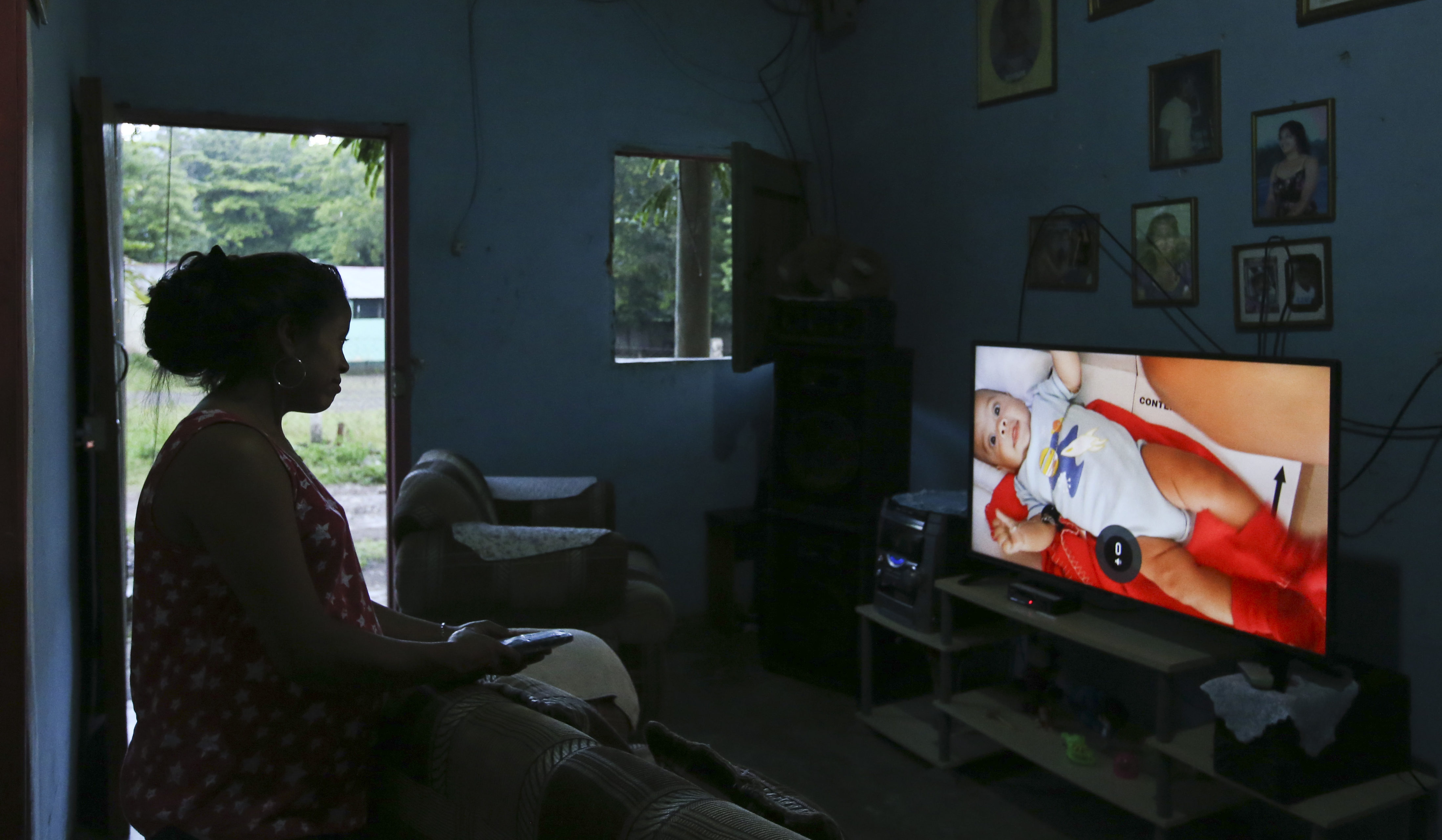 In this July 18, 2018 photo Adalicia Montecinos watches a video at her home, in La Libertad, Honduras of her son Johan Bueso Castillo who was separated from his father at the Texas border. Montecinos watches videos of her infant son Johan over and over again. She had recorded each month of his life before he left for the United States with his father. (AP Photo/Esteban Felix)