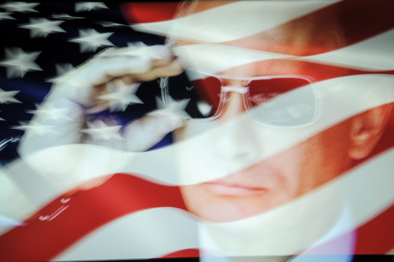 An American flag is seen with a portrait of Russian president Vladimir Putin in this photo illustration on October 31, 2017. Material posted on Facebok and other social media directly and indirectly reached over 126 million Americans between 2015 and 2017 according to a company testimony that will be presented to the US Senate judiciary committe on Tuesday. (Photo by Jaap Arriens/NurPhoto)