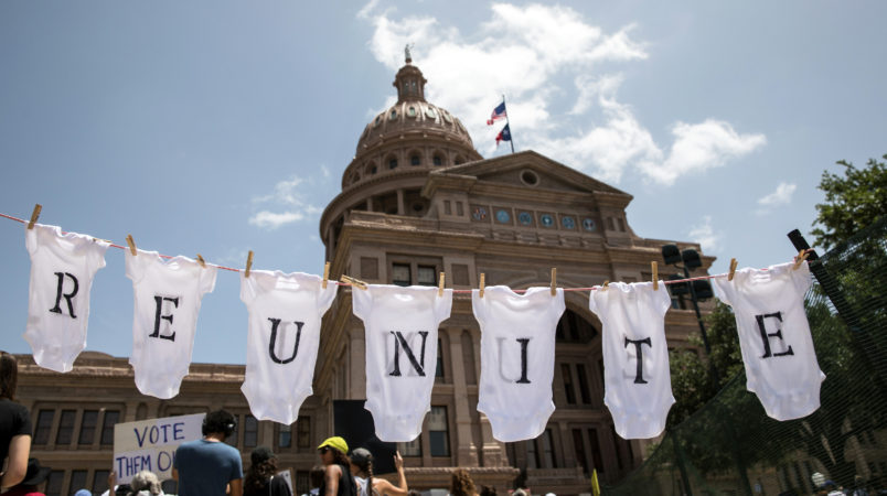 """AUSTIN, TX - JUNE 30: A demonstrator uses baby clothes to spell out the word """"reunite"""" during a rally against the Trump administration's immigration policies outside the Texas Capitol in Austin, Texas, on June 30, 2018. Demonstrations are being held in cities across the U.S. Saturday to call for the reunification of separated families and to protest the detention of children and families seeking asylum at the border. (Photo by Tamir Kalifa/Getty Images)"""