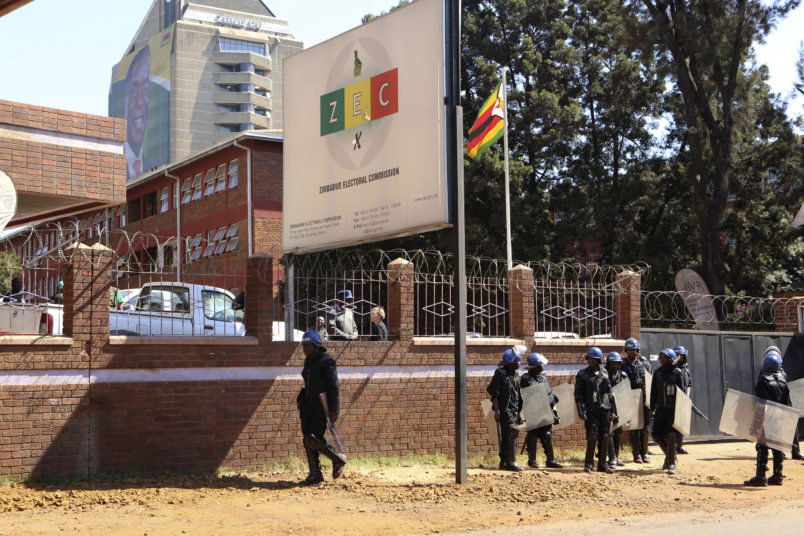 A portrait of Zimbabwean President Emmerson Mnangagawa is seen at the party headquarters as police  walk past the Zimbabwe Electoral Commission offices after  they blocked dozens of opposition party supporters  from entering the  commission offices in  Harare,  Zimbabwe,Wednesday, Aug, 1, 2018. Zimbabweans are awaiting the  first results from an election that they hope will lift the country out of economic and poltical stagnation  after decades of  rule by former leader Robert Mugabe (AP Photo/Tsvangirayi Mukwazhi)