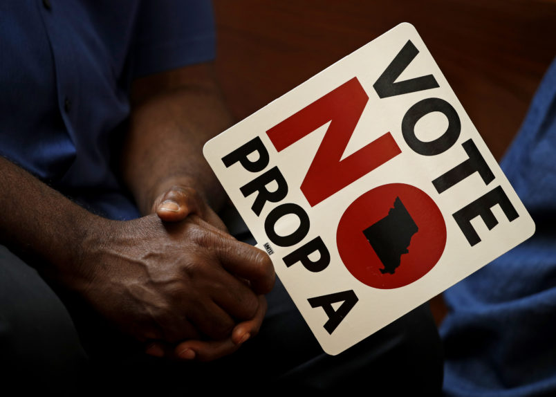 ** HOLD FOR USE WITH STORY BY DAVID LIEB ** In this photo taken Tuesday, July 31, 2018, people opposing Proposition A listen to a speaker during a rally in Kansas City, Mo. Missouri votes Tuesday on a so-called right-to-work law, a voter referendum seeking to ban compulsory union fees in all private-sector workplaces. (AP Photo/Charlie Riedel)