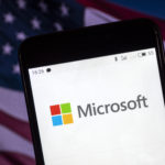 KIEV, UKRAINE - 2018/08/06: The Microsoft logo seen displayed on a smart phone with a background of an American Flag. According to the New York Stock Exchange (NYSE), the company is on the fourth place at the market value in the world - $ 825.8 billion. (Photo by Igor Golovniov/SOPA Images/LightRocket via Getty Images)