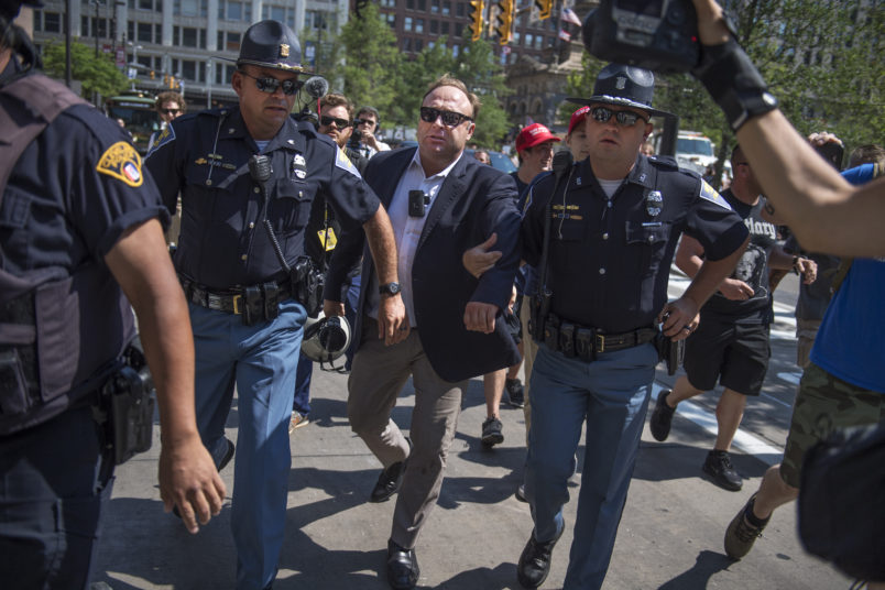 UNITED STATES - JULY 19: Radio host Alex Jones is escorted from a rally in the Public Square after inciting a confrontation near the Republican National Convention at the Quicken Loans Arena in Cleveland, Ohio, July 19, 2016. (Photo By Tom Williams/CQ Roll Call)