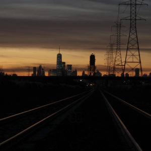 LYNDHURST, NJ - NOVEMBER 4: Train tracks lead to New York City as the sun rises behind lower Manhattan and One World Trade Center on November 4, 2017, as seen from Lyndhurst, New Jersey. (Photo by Gary Hershorn/Getty Images)