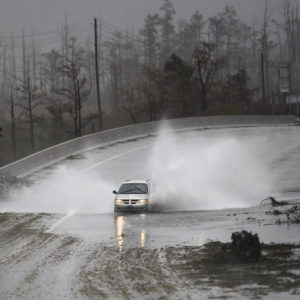 A car drives through water on U.S. 74/76 in Leland, N.C., Saturday, September 15, 2018. The rain from Hurricane Florence was expected to continue through Sunday.         [Matt Born/StarNews Photo]
