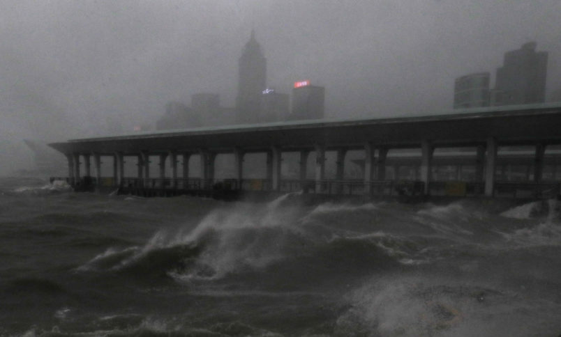Strong wind caused by Typhoon Mangkhut  is seen on the waterfront of Victoria Habour Hong Kong, Sunday, Sept. 16, 2018. Hong Kong and southern China hunkered down as strong winds and heavy rain from Typhoon Mangkhut lash the densely populated coast. The biggest storm of the year left at least 28 dead from landslides and drownings as it sliced through the northern Philippines. (AP Photo/Vincent Yu)