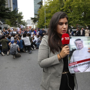"""A journalist holding a poster with a photo of the missing Saudi writer Jamal Khashoggi, makes a piece on camera while covering a protest in his support near the Saudi Arabia consulate in Istanbul, Monday, Oct. 8, 2018.Turkish officials have said they believe that the journalist was slain in """"a preplanned murder"""" at the kingdom's consulate and that his body was later removed. Saudi officials have denied the allegations as baseless.(AP Photo/Lefteris Pitarakis)"""