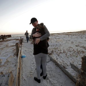 Matthew Fortner hugs his mother Lavonia Fortner, as they walk to view the beach for what they feel is the last time, after they sifted through the rubble of her father-in-laws destroyed home, in the aftermath of Hurricane Michael in Mexico Beach, Fla., Saturday, Oct. 13, 2018. John E. Fortner, not pictured, a Mexico Beach resident, came with his family to find memorabilia his wife collected, which is now scattered amidst the rubble of his obliterated home. (AP Photo/Gerald Herbert)