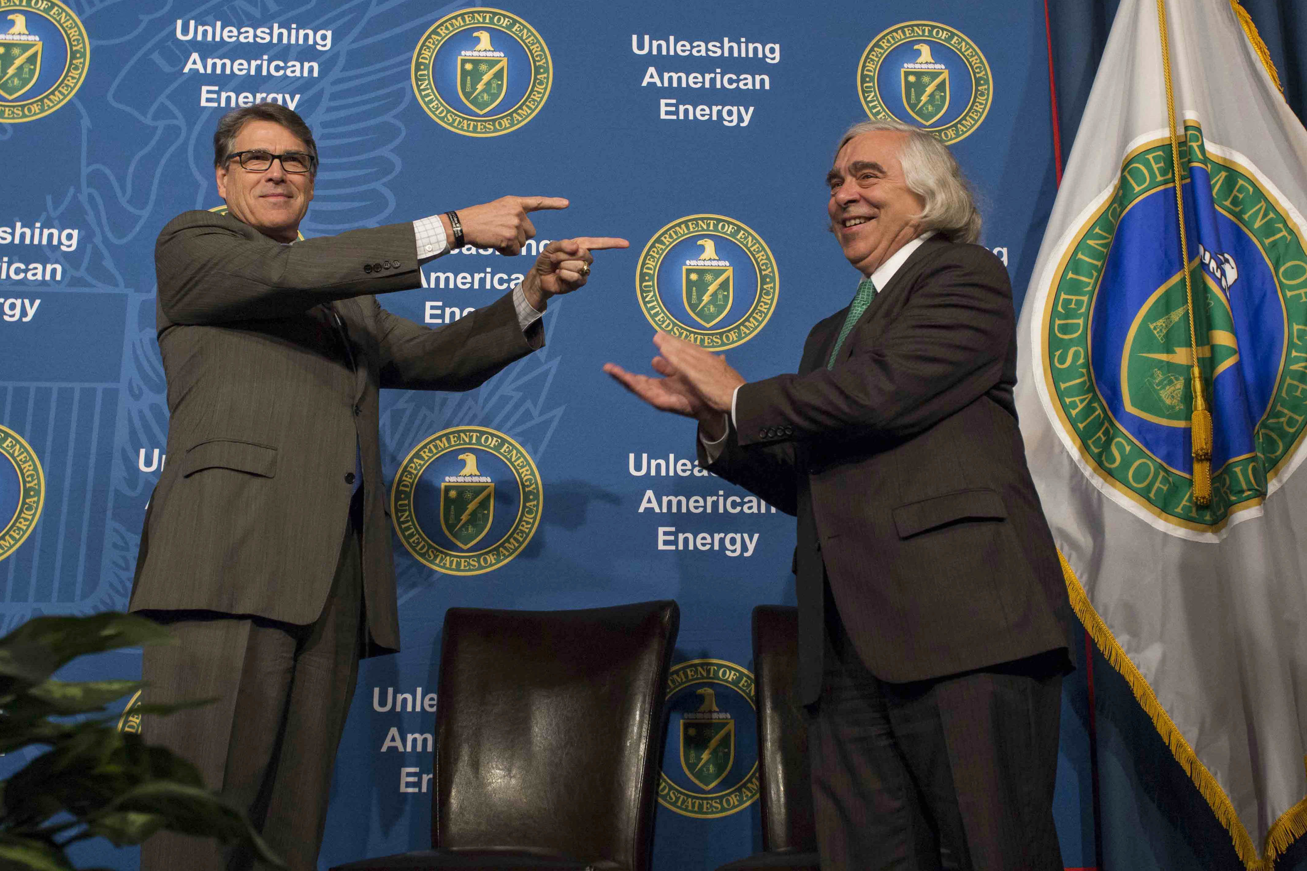 In this Aug. 2, 2018 photo made available by the U.S. Department of Energy, Energy Secretary Rick Perry welcoming his predecessor, Ernest Moniz, during the unveiling of Moniz's portrait. Simon Edelman/U.S. Department of Energy     https://www.flickr.com/photos/departmentofenergy/36202965571/in/photolist-ny1wad-XigXwL-XigXHs-Xa8EU6-N7N3cM-Xa8F2v-XigXA3-Xa8EJX-Xa8EEZ-Xa8F7F-Xa8ETe-X7i1W1-Xa8F3H-bF5Abh-vE7kH9-KZnGYL-X5pZHf-224K5Jp-DVPeYm-224K5sT-DVPfAU-224K572-fkwAbh-Xa8Enz-CqdLEn-2222eqQ-224KUu4-224Lmr4-CqdM12-CqdN8x