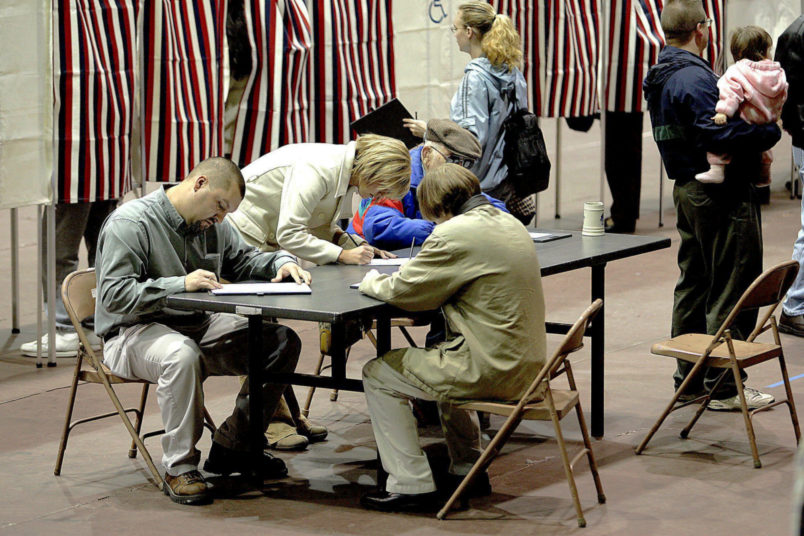 A group of voters fill out their ballots at a table rather than wait for an empty voting booth Tuesday, Nov. 2, 2004, at the Civic Center in Dodge City, Kan. Depending on their precinct, voters had to wait in line to receive a ballot and some had to wait in line for an empty booth. (AP Photo/Dodge City Daily Globe, Michael Schweitzer)