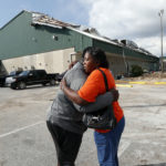 Franlisa Smith, whose son Nick Smith is a defensive lineman on the Mosley High football team, hugs defensive line coach William Mosley at the start of practice at the school, which was heavily damaged from Hurricane Michael, in Lynn Haven, Fla., Friday, Oct. 19, 2018. (AP Photo/Gerald Herbert)
