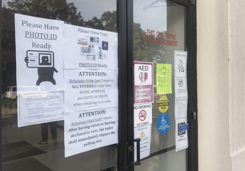 A sign outside the Pulaski County Regional Building in Little Rock, Ark., advises voters on Monday, Oct. 22, 2018, of a state law requiring them to show photo identification before casting a ballot. Early voting began Monday for Arkansas' November 6 midterm election. (AP Photo/Andrew DeMillo)
