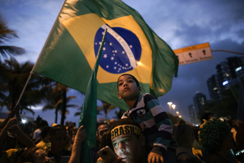 Supporters stand with is kid on the shoulders as he wait for the speech of Jair Bolsonaro in front of his residence in Rio de Janeiro, Brazil, Sunday, Oct. 28, 2018. Brazil's Supreme Electoral Tribunal declared the far-right congressman the next president of Latin America's biggest country. (AP Photo/Leo Correa)