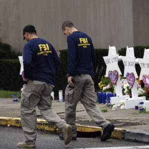 "Members of the FBI walk past a memorial outside the Tree of Life synagogue after a shooting there left 11 people dead in the Squirrel Hill neighborhood of Pittsburgh on October 27. - Mourners held an emotional vigil Sunday for victims of a fatal shooting at a Pittsburgh synagogue, an assault that saw a gunman who said he ""wanted all Jews to die"" open fire on a mostly elderly group. Americans had earlier learned the identities of the 11 people killed in the brutal assault at the Tree of Life synagogue, including 97-year-old Rose Mallinger and couple Sylvan and Bernice Simon, both in their 80s.Nine of the victims were 65 or older. (Photo by Brendan SMIALOWSKI / AFP)        (Photo credit should read BRENDAN SMIALOWSKI/AFP/Getty Images)"