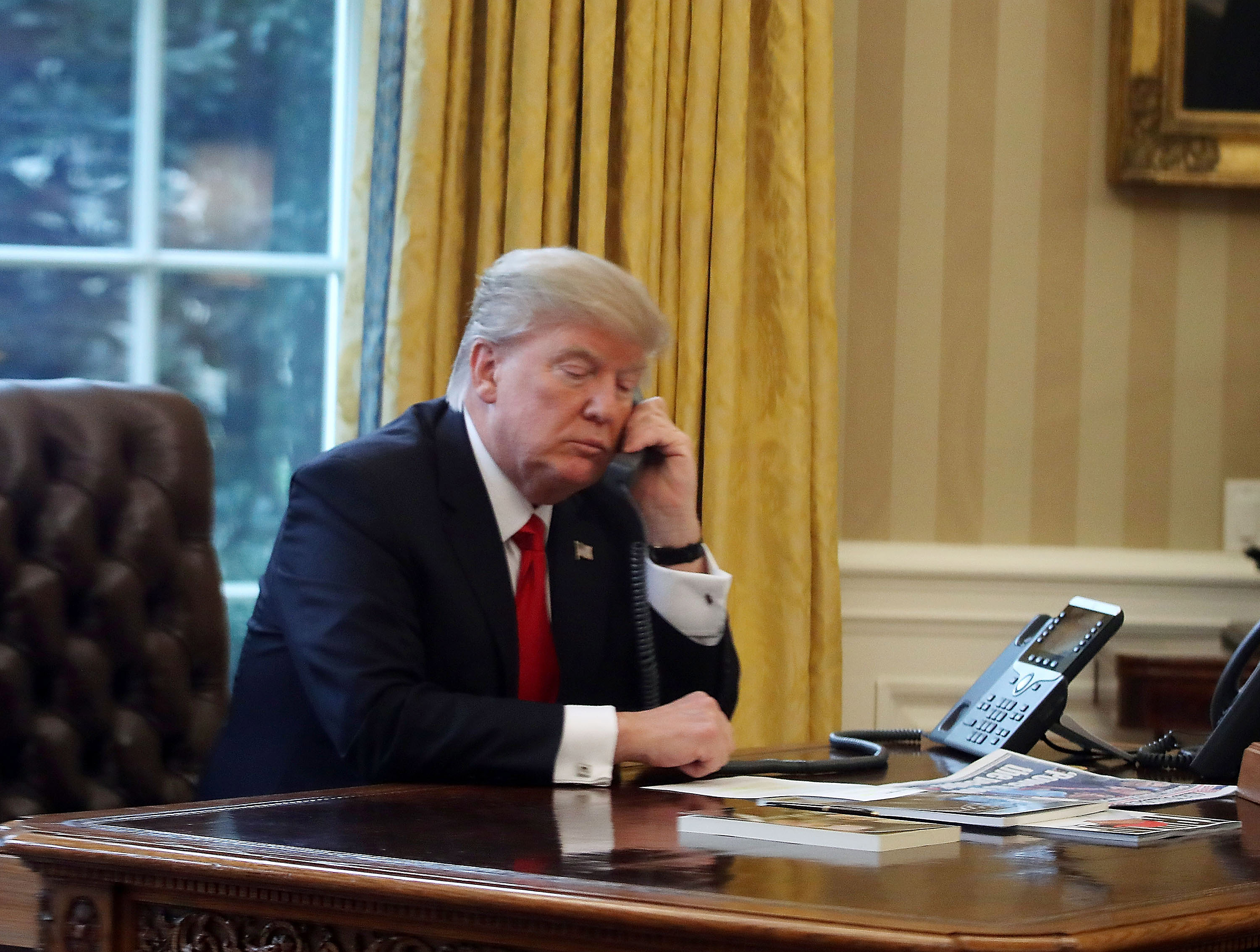 WASHINGTON, DC - JANUARY 29:  President Donald Trump is seen through a window speaking on the phone with King of Saudi Arabia, Salman bin Abd al-Aziz Al Saud, in the Oval Office of the White House, January 29, 2017 in Washington, DC. On Sunday, President Trump is making several phone calls with world leaders from the Oval Office.  (Photo by Mark Wilson/Getty Images)