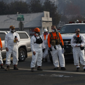First responders look on as the motorcade of President Donald Trump visits a neighborhood impacted by the wildfires, Saturday, Nov. 17, 2018, in Paradise, Calif. (AP Photo/Evan Vucci)